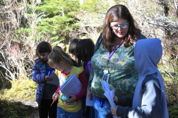 Allie Smith talks to one of her second grade students during a nature walk Tuesday afternoon. (Photo by Lisa Phu/KTOO)