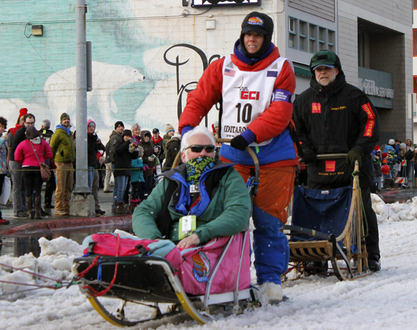 Cindy Abbott cruises through Anchorage during the 2015 Iditarod ceremonial start. (Photo by Josh Edge, APRN - Anchorage)