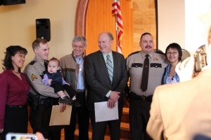 VPSOs Michael Gagliano (second from left) and James Hoelscher (second from right) pose for pictures with their families, Gov. Bill Walker and Lt. Gov. Byron Mallott. (Rachel Waldholz/KCAW)