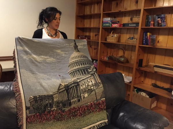 In the den, Kara Nelson holds up a blanket given to Haven House by U.S. Sen. Lisa Murkowski. (Photo by Lisa Phu/KTOO)