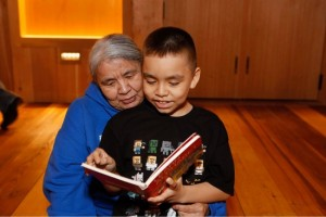 Betty Ann Samato reads a book with her grandson Bryson Stepetin at a Baby Raven Reads family night. (Photo by Brian Wallace/Courtesy Sealaska Heritage Institute)