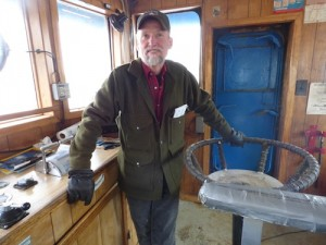 Dan Magone stands in the wheelhouse of the salvage vessel Redeemer. (Annie Ropeik/KUCB)