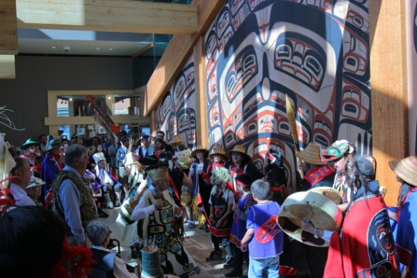 Singers in front of the newly unveiled artwork on the clan house (Photo by David Purdy/KTOO)