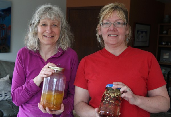 Denise Lisac and Lynn Van Vactor holding carrot and rose hip infusions. (Photo by Hannah Colton, KDLG – Dillingham)
