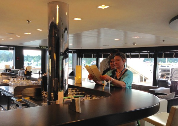 Petersburg chef, Mindy Anderson, and Liz Cabrera with the Petersburg Borough check out a menu at one of the ship's bars. Photo/Angela Denning