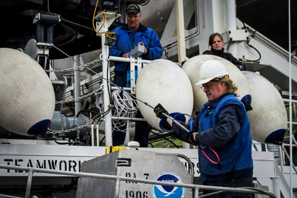 Chief Bosun Jim Kruger (front) works with Jason Kinyon and Lindsey Houska on the NOAA ship Rainier to prepare for the summer's first Arctic survey project, in Kotzebue Sound. (Photo: Courtesy of NOAA)