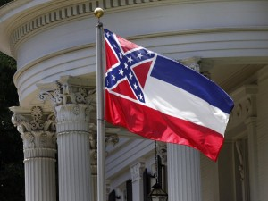 The state flag of Mississippi is unfurled against the front of the Governor's Mansion in Jackson. Photo via NPR.
