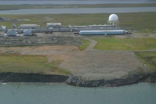 This oblique aerial photograph from 2006 shows the Barter Island long-range radar station landfill threatened by coastal erosion. The landfill was subsequently relocated further inland, however, the coastal bluffs continue to retreat. Photo by Bruce Richmond/Ann Gibbs, USGS.