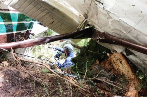NTSB investigator Brice Banning examines the wreckage of the sightseeing plane that crashed June 25th in Misty Fjords south of Ketchikan. Shared via KRBD-Ketchikan.