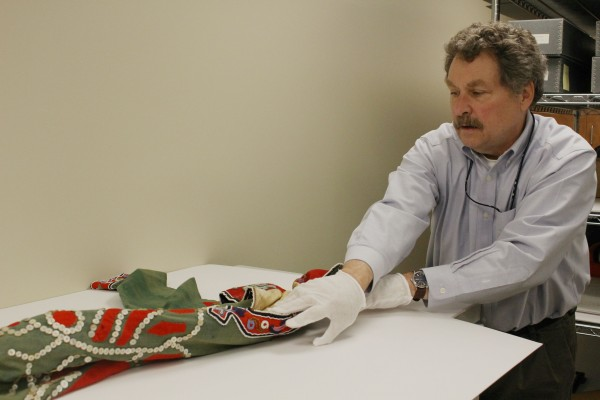 Chuck Smythe unrolls the tunic from storage. It's kept this way to avoid damage. (Photo by Elizabeth Jenkins/KTOO)