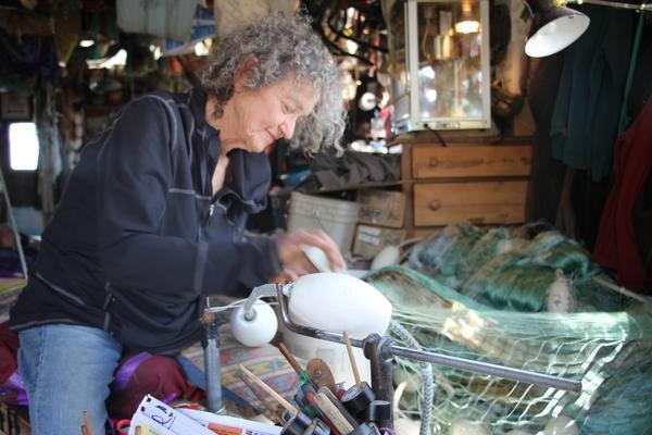 Marcia Dale expertly hangs nets at Watzituya. Credit Hannah Colton/KDLG