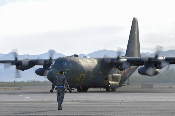 A Japanese Air Self-Defense Force airman directs a taxiing C-130H Hercules on Joint Base Elmendorf-Richardson, Alaska, Aug. 11, 2015. The JASDF contingent is on JBER to participate in Red Flag 15-3, a series of Pacific Air Forces commander-directed training exercises for U.S. and international forces to provide joint offensive, counter-air, interdiction, close air support, and large force employment in a simulated combat environment. (U.S. Air Force photo/Alejandro Pena)