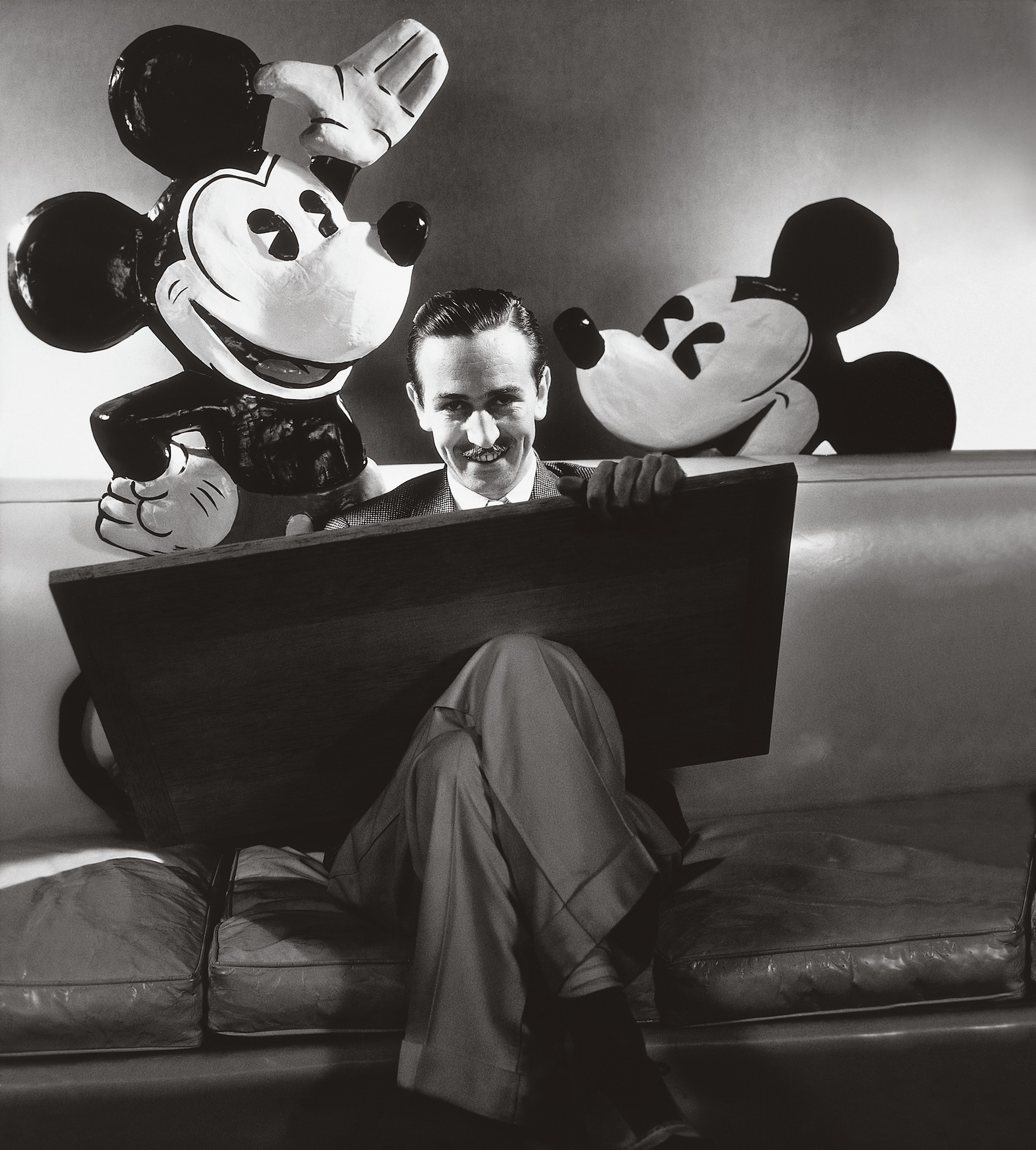 ca. October 1933, USA --- Walt Disney seated with drawing board on his lap and representations of his creations Mickey and Minnie Mouse behind. (Photo Courtesy of © Condé Nast Archive/Corbis)