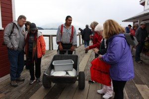 An employee in uniform answers tourists questions about a real halibut carted around the boardwalk. (Photo by Elizabeth Jenkins/KTOO)
