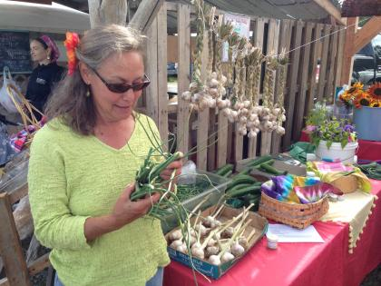 Lori Jenkins of Synergy Gardens holds garlic scapes her WWOOFers helped harvest - Photo by Shady Grove Oliver/KBBI