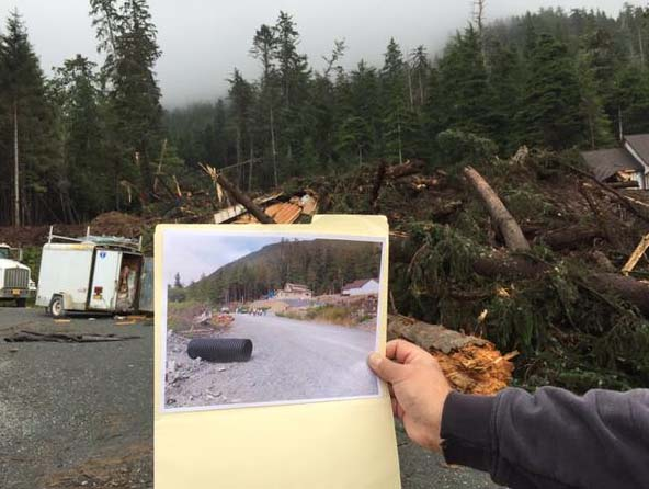 "Governor Walker holds up a ""before"" photo against a a backdrop of damages from the Sitka landslides. Gov. Walker is in Sitka on Aug. 19 surveying the damage. Photo: Governor's office."