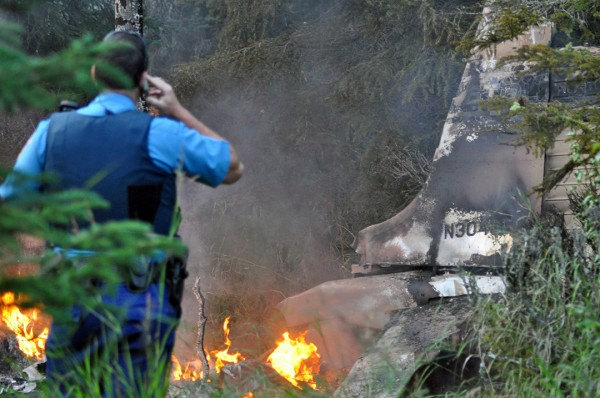 Photo courtesy of Joseph Robertia, Redoubt Reporter. An Alaska State Trooper, the first responder on the scene, surveys a plane crash in Kasilof on Saturday.