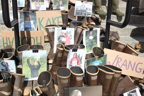 About a hundred pairs of the brown rubber boots along with photos of Alaskans were on the steps of the Capitol building to protest mines in British Columbia. Photo: Lisa Phu/KTOO.