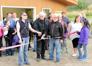 Project manager Michelle Anderson, Village President Clemens Grunert Jr., and Lake and Pen Borough Mayor Glen Alsworth pose for a photo at the official ribbon cutting of the Packer Creek hydro project. (Photo by Hannah Colton, KDLG - Dillingham)