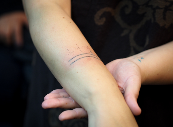 Holly Mititquq Nordlum shows off her partially complete tattoo during a live demonstration at Anchorage's Above The Rest studio. Each horizontal line is 40 individual stitch marks through the first layer of skin. Before starting the stitches, Jacobsen poked the basic design of three bird feet rising from the lines. Nordlum's Inupiaq name, Mititquq, means a place where birds land, and she commemorates achieving big life goals with bird feet tattoos, like the two on her opposite wrist, done with a tattoo gun. (Photo: Zachariah Hughes, KSKA)