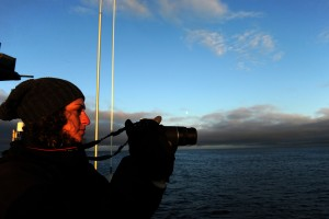 Katherine Robbins photographs the sunset from the US Fish and Wildlife Service research boat R/V Tiglax as sails from Adak Islands on a cruise to Attu Island in the Aleutian Islands, in western Alaska, on Sunday, May 31, 2015. Robbins from Memorial University of Newfoundland in St. John Newfoundland will be dropped of at Buldir Island where she will be studying Auklets. (Bob Hallinen / Alaska Dispatch News)