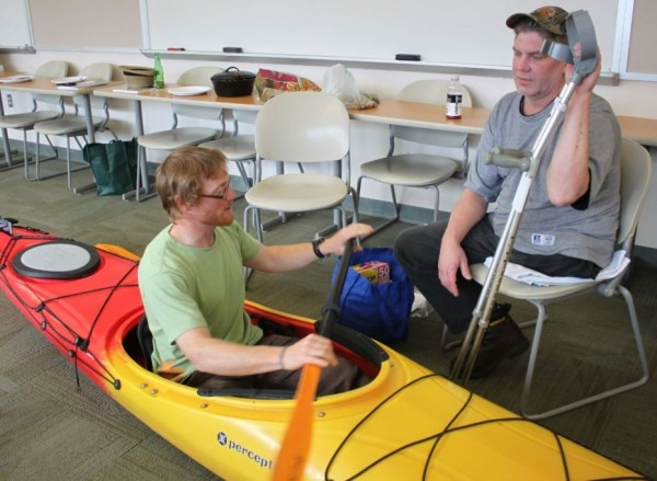 Above and Beyond Alaska employee Corey Denton explains kayak basics to J.C. Terrill during an ORCA adaptive kayak training. (Photo by Lisa Phu/KTOO)