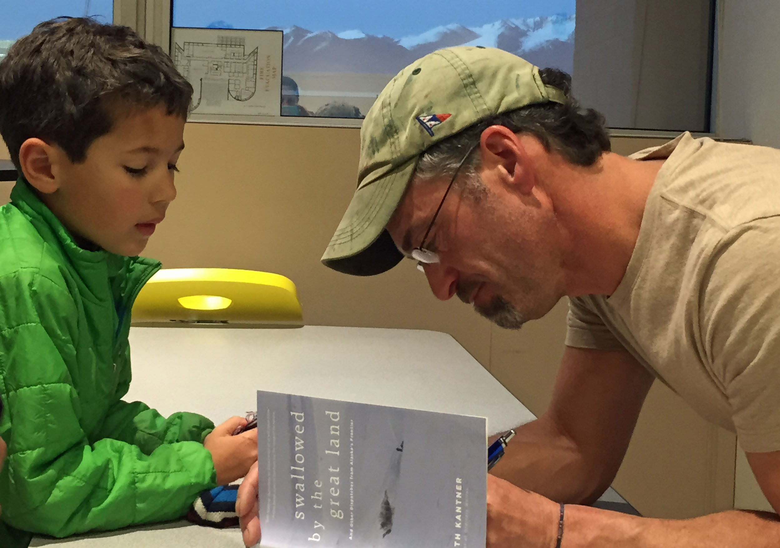 Seth Kantner signs a copy of his new book for a young fan. (Photo by Lori Townsend/APRN)