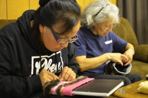 Stacey Skan and Anna Frisby sew sea otter fur onto knit headbands as a donation to Hydaburg's Artist Co-op. Photo: Ruth Eddy/KRBD.