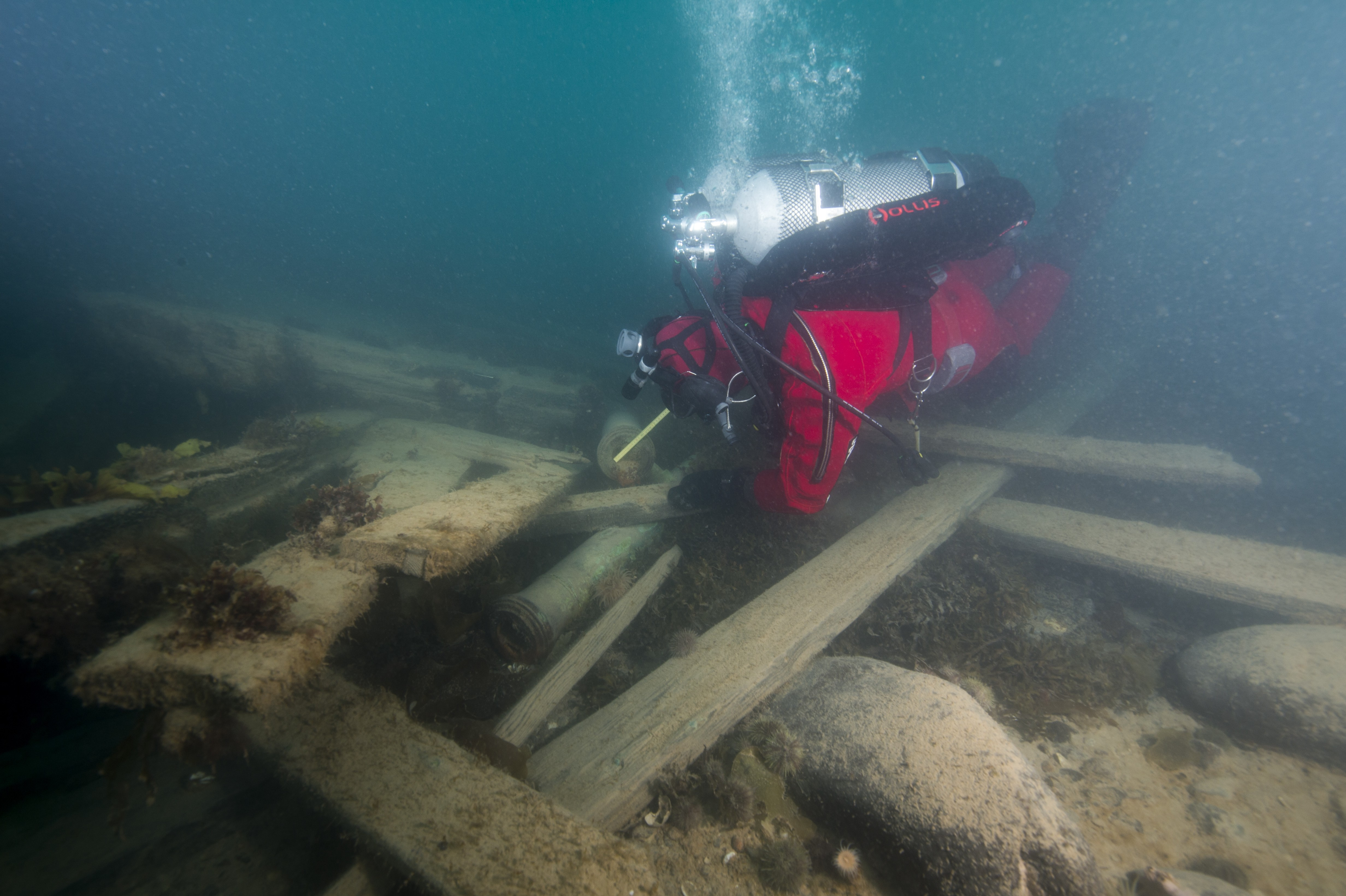 Cannons and loose timbers on the starboard stern.  Diver Filippo Ronca taking measurements at the muzzle. (Photo Courtesy of WGBH.)