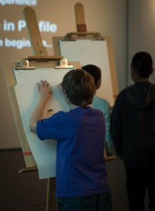 Middle schoolers try there hands at sketching portraits in profile, guided a short video. The easels will be up for the remainder of the exhibit. (Photo: Zachariah Hughes, KSKA)