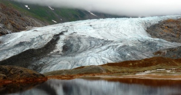 A glacier reflects in a naturally occurring pool of rusty, acidic water at the site of one of the KSM prospect's planned open-pit mines. (Photo by Ed Schoenfeld/ CoastAlaska News).