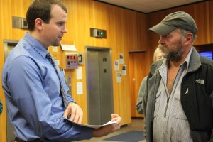 In the lobby of the Dimond Courthourse on Monday morning, attorney Nick Polasky hands trapper John Forrest court documents before the trial. Polasky is Kathleen Turley's lawyer. (Photo by Lisa Phu/KTOO)