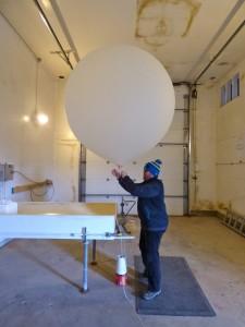 William Wells prepares a weather balloon for launch. (KUCB/John Ryan photo)