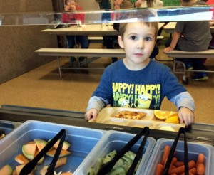 A student at the Bristol Bay Borough School chooses oranges from the salad bar. CREDIT TANYA DUBE. Shared via kdlg.org.