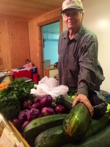 Shopper checks out locally grown vegetables. (Photo by Daysha Eaton/KBBI)