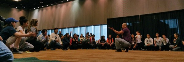 Xeetli.eesh Lyle James, a group leader for the Woosh.ji.een dancers in Juneau, teaches a small crowd of young people during a break out session at the Elders and Youth Conference in Anchorage. (Photo by Jennifer Canfield/KTOO)