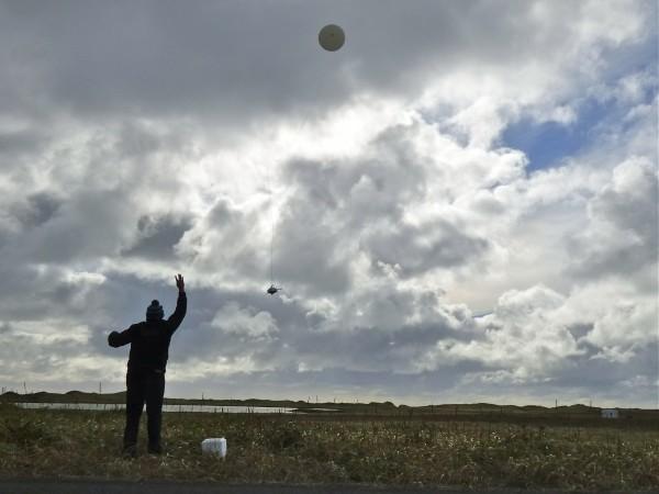 William Wells releases a weather balloon on Alaska's St. Paul Island. (KUCB/John Ryan photo)
