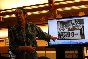 Sam gives a presentation at the library. He points to a picture of himself with Tlingit elders, who encouraged him to pursue his interest in cemetery caretaking. (Photo courtesy of Bob Sam)