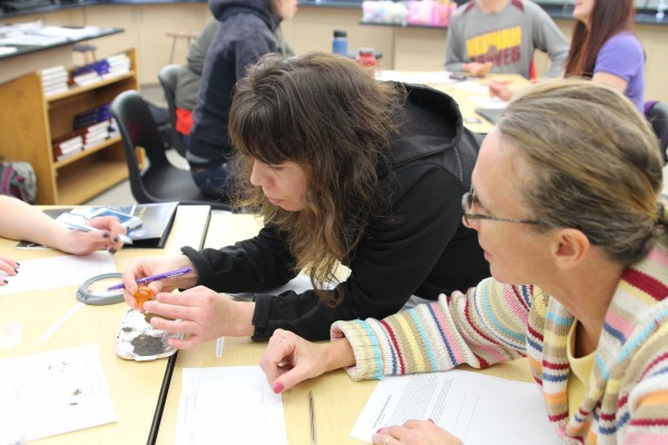 Teachers examine artificial moon and Mars soil at the Alaska Math and Science Conference, held at Sitka High School. (Brielle Schaeffer/KCAW photo)