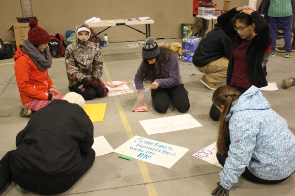During the sleep-out, students made signs about youth homelessness that they waved outside Mendenhall Mall and Safeway. (Photo by Lisa Phu/KTOO)
