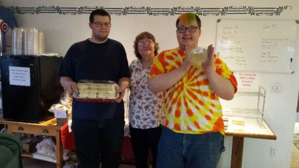 (Left to right) Sam, Karin, and Ben Stahlhut stand in front of their display table in their home and business, Simply Awesome Bakery. Kayla Desroches/KMXT