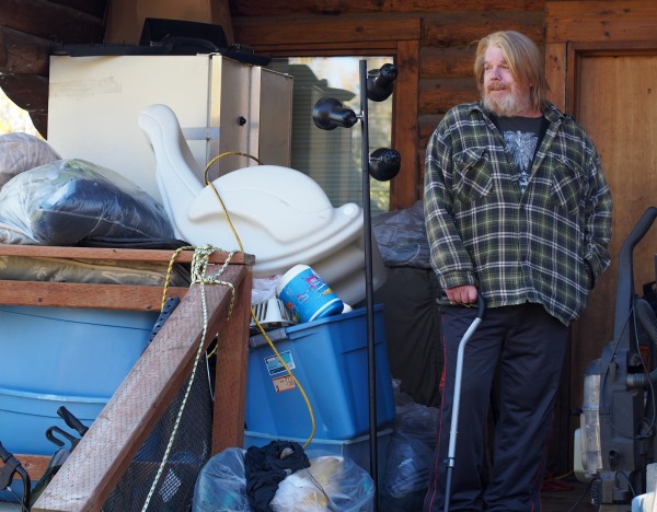 Scott Harrison standing outside the cabin he rents in Big Lake. It's too small inside for him to fit many of his possessions, so he keeps more durable items like clothes and dry-goods outside. Photo: Zachariah Hughes, KSKA