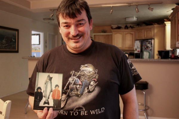 Rob Kenney holds a childhood picture of him and his brother next to a king salmon. (Photo by Lisa Phu/KTOO)