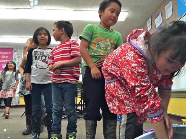 "St. Paul students line up to stick their hands inside ""blubber mitts"" (Crisco-lined plastic bags) to learn how marine mammals stay warm in the icy Bering Sea. KUCB PHOTO/JOHN RYAN"