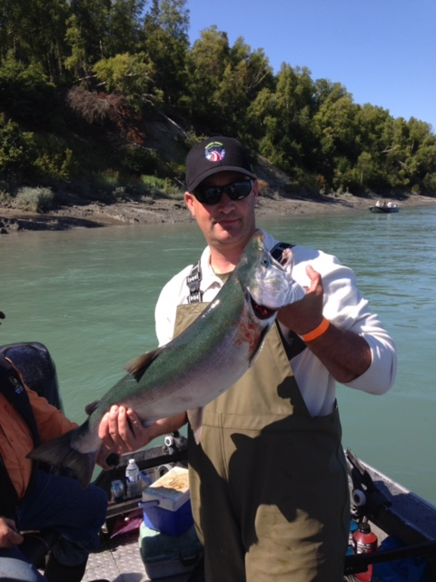 Staff Sergeant Joshua Schneiderman, a forward observer stationed with the 4th Brigade 25th Infantry Division, holding a silver salmon caught during a Wounded Warriors event.