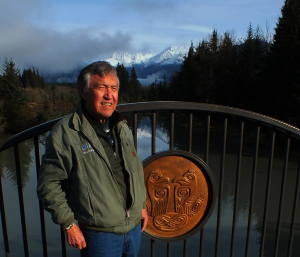Roy Peratrovich Jr. stands next to one of the bronze medallions he designed for the first Brotherhood Bridge created in 1965. The medallions were recovered, restored and installed on the new Brotherhood Bridge that was dedicated on Saturday. (Photo by Matt Miller/KTOO)