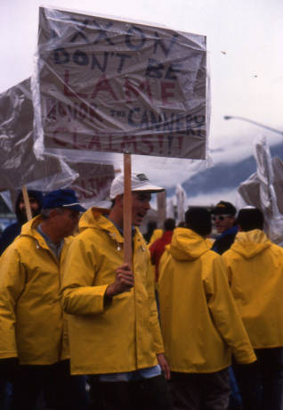 "Seafood processors picketing and protest at Exxon's headquarters. Their signs read, ""Exxon, don't be lame, honor the cannery claims."" Photo: Alaska Office of the Governor. Accessed via Alaska Digital Archives."
