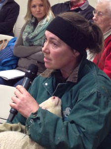 Large animal veterinarian Sabrieta Holland takes the mic with a lamb in her care. Photo: Ellen Lockyer/KSKA-Anchorage.