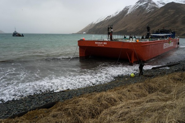 The bright orange Resolve Ibis (far left), an oil spill response barge capable of sopping up over 20,000 gallons of fuel, has a five-year mooring permit from the Alaska Department of Natural Resources. CREDIT ETHAN NICHOLS