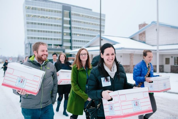 Immediately after a press conference in downtown Anchorage this morning, a large parade of supporters carried signature boxes and banners across the street to the Division of Elections. Photo courtesy PFD Voter Registration campaign.